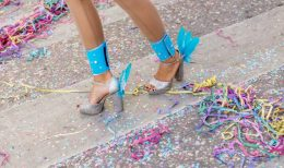 Legs and shoes girls at the carnival. Scattered confetti.